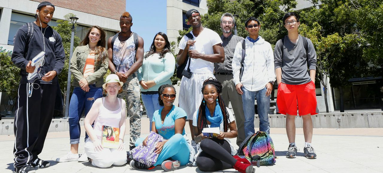 Diverse group of ten students with their professor, smiling on the main Laney College quad