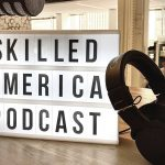 Living room in home with microphone, headphones and sign that says: Skilled America Podcast