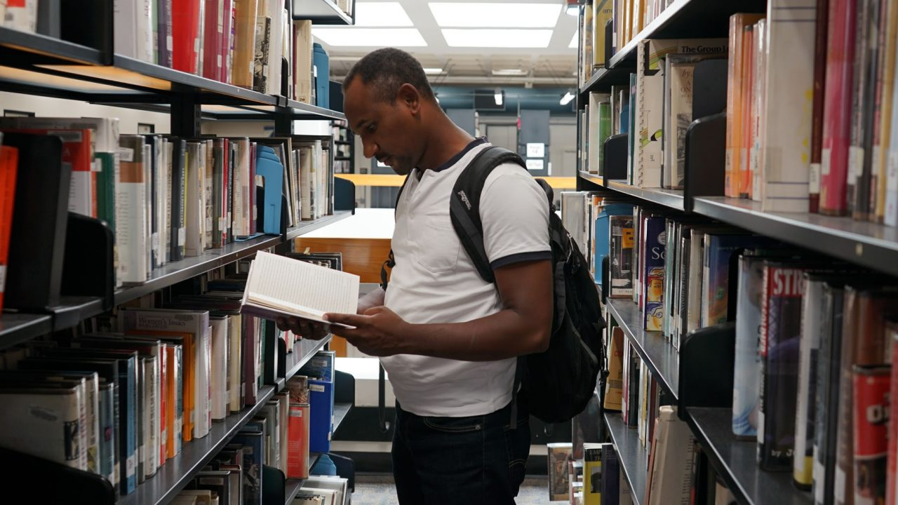 Student at the library looking at a book
